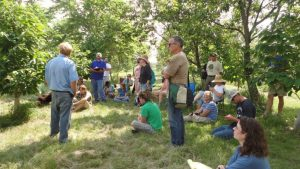 Agroforestry class listens to Tom Wahl near pawpaw grove.